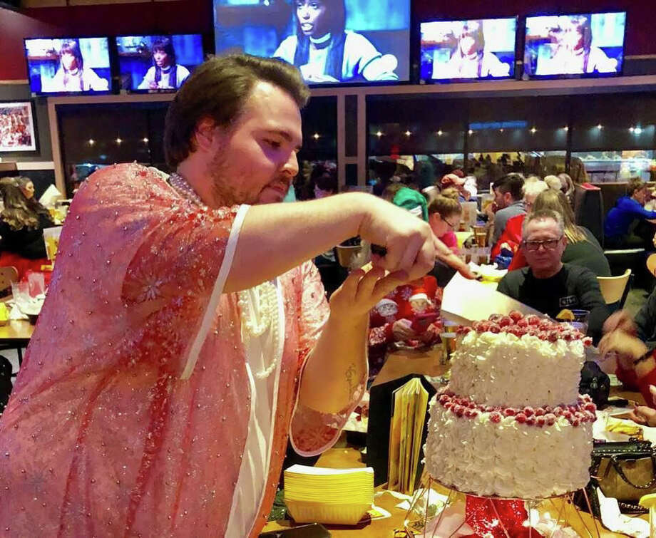 Nolan Schooley cuts a three-tier cake he made for  friends and family Monday night as they watched him compete in Food Network's Holiday Baking Championship. (photo provided) Photo: Photo Provided