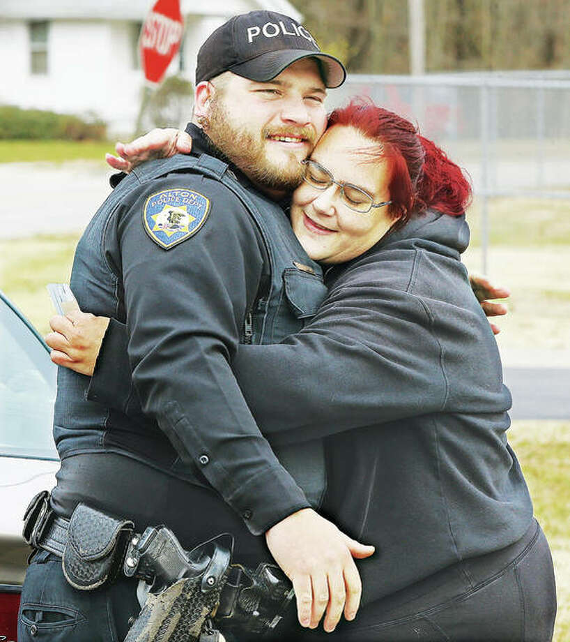 "Angela Anderson of East Alton gives a big hug to Alton police officer Pfc. Elliott Fergurson Thursday after getting a $50 gift card to Aldi during last year's ""Summons of Joy"" giveaway. The Alton Police Department will once again be raising money for a good cause with a ""No Shave November"" campaign this month. Photo: John Badman 