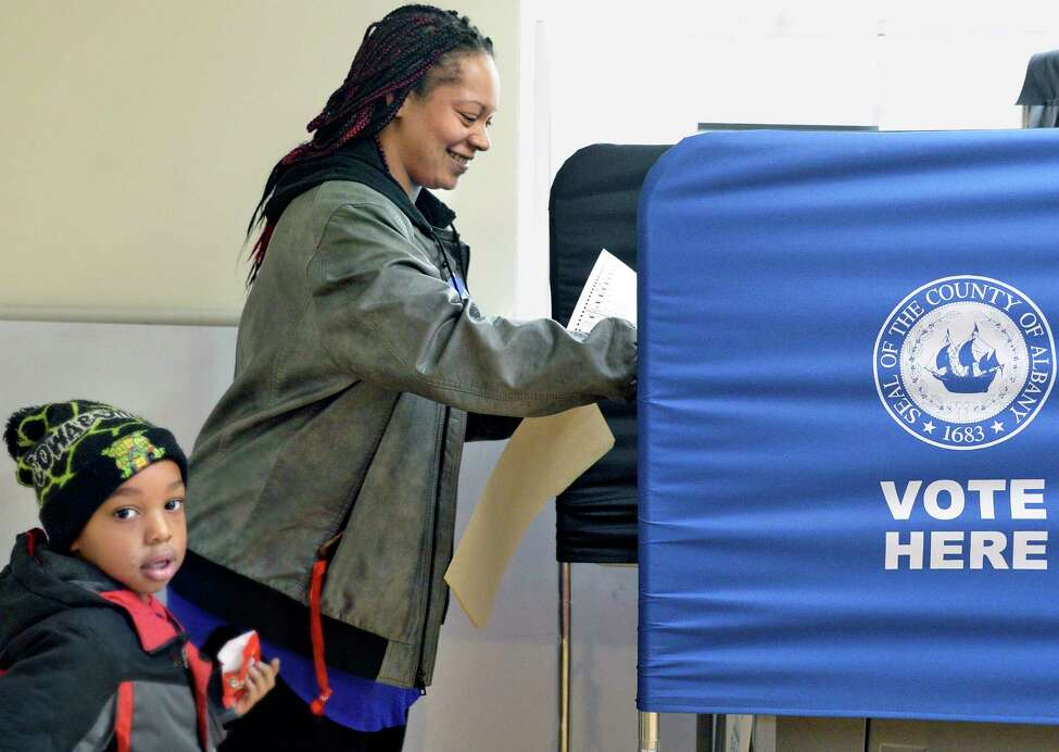 Nichole Potter casts her ballot as son Zion, 4, looks on at the Ward 3 polling station on Orange Street Tuesday Nov. 6, 2018 in Albany, NY. (John Carl D'Annibale/Times Union)