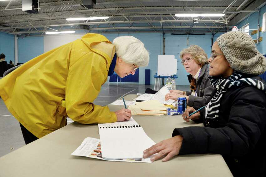 Susan DuBois, left, signs in to vote with election inspectors Wendy Lindskoog and Joanna Puertas, right, at the Parks & Recreation Department Tuesday Nov. 6, 2018 in Albany, NY. (John Carl D'Annibale/Times Union)