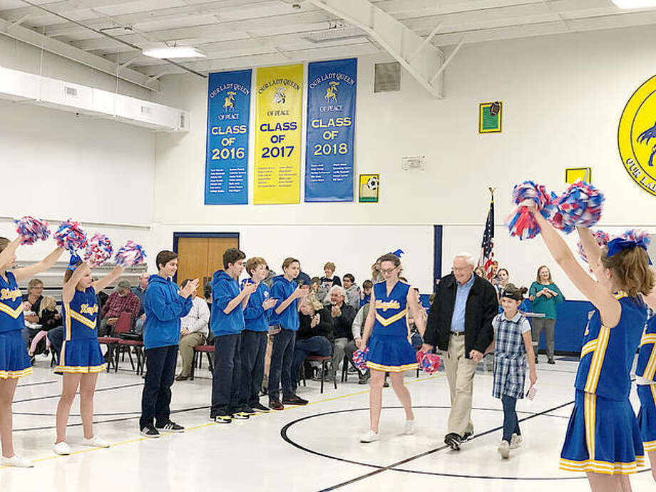 Our Lady Queen of Peace students escort a veteran to the front of the school's gymnasium Tuesday during OLQP's annual Veterans Day Thank You Program. More than 30 veterans were recognized at the Bethalto school's ceremony. Photo: For The Telegraph