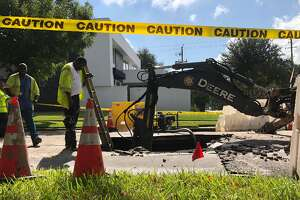 Workers repair a sinkhole in the Montrose area on Tuesday, Nov. 6, 2018.
