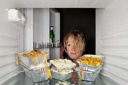 A woman looking at old take-away food containers left in the refrigerator.