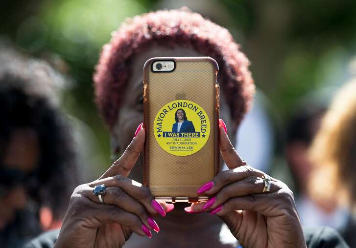 Lahoma Tugbenyoh of Pittsburg takes a picture on her phone while sporting a commemorative sticker before the inauguration ceremony for Mayor London Breed on the steps of City Hall in San Francisco, Calif. Wednesday, July 11, 2018.
