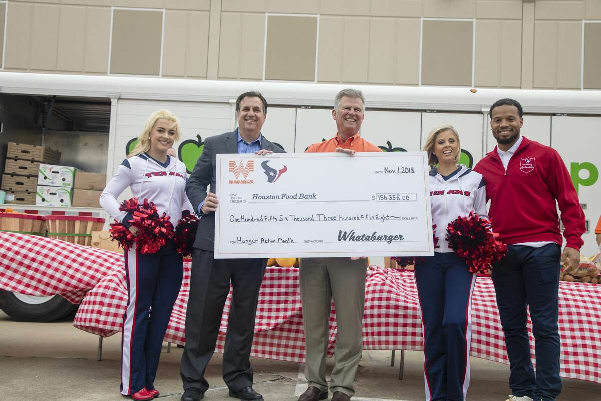 Whataburger executives, Houston Texans ambassador Cecil Shorts, and the Texans cheerleaders presented a check to the Houston Food Bank.