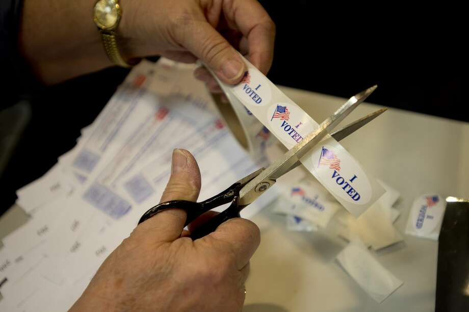 FILE — A voting official cuts a roll of stickers as voters cast their ballots in the midterm elections on Tuesday, Nov. 6, 2018 at City Hall in Midland. (Katy Kildee/kkildee@mdn.net) Photo: (Katy Kildee/kkildee@mdn.net)