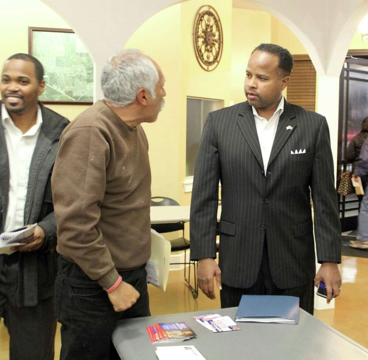 State Rep. Ron Reynolds(center) speaks with a resident at a recent town hall meeting in Fresno.