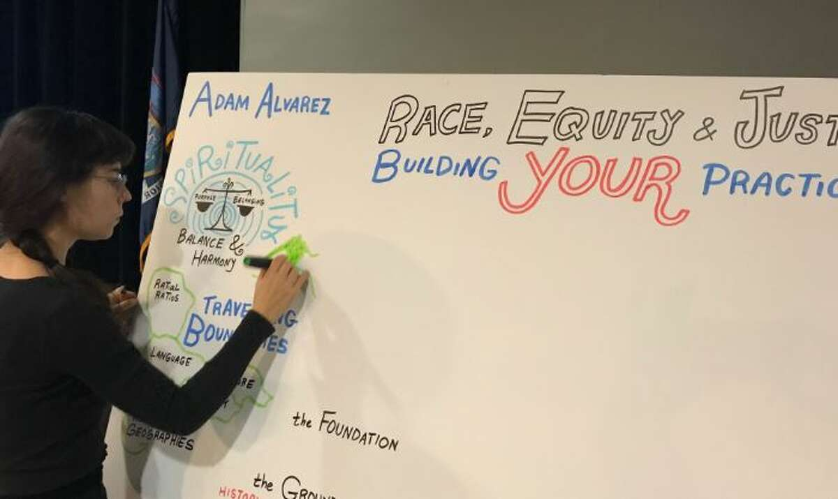 Graphic recorder Ona Rygelis takes some visual notes during Tuesday's Urban Schools conference