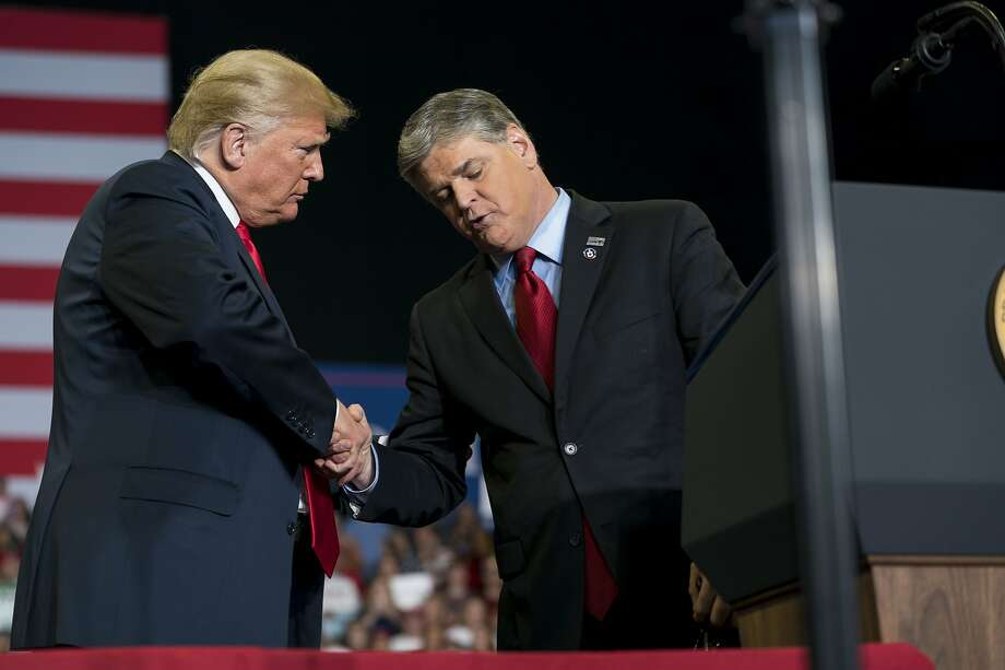 President Trump greets Sean Hannity onstage during a rally in Cape Girardeau, Mo. Trump was joined by a trio of conservative media stars as he wrapped up his midterm election campaign. Photo: Doug Mills / New York Times