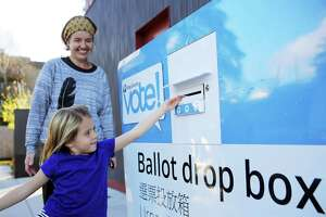Sophie Schlitz, 5, pushes in a ballot for her mom, Liz, at the ballot drop box in White Center, Tuesday,  Nov. 6, 2018. A constant stream of people stopped by to drop off their ballots throughout midterm election day.