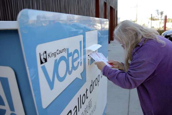 A woman drops off her ballot at the drop box in White Center, Tuesday, Nov. 6, 2018. A constant stream of people stopped by to drop off their ballots throughout midterm election day.