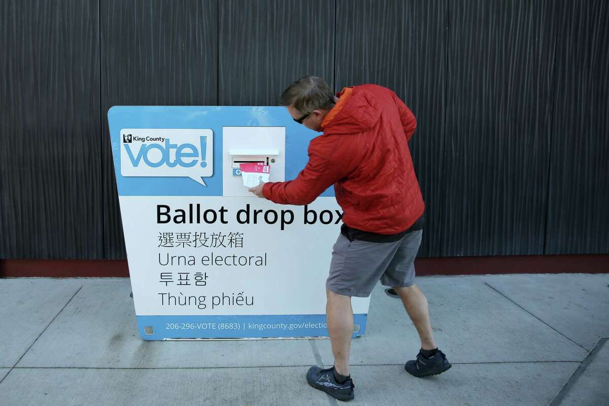 A man drops off his ballot at the drop box in White Center, Tuesday, Nov. 6, 2018. A constant stream of people stopped by to drop off their ballots throughout midterm election day.