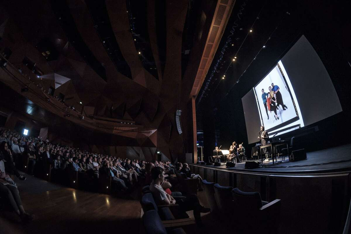 """Photo of Kronos Quartet and filmmaker Sam Green performing and screening the live documentary """"A Thousand Thoughts."""""""