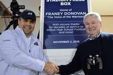 Brian Colburn, representing the Wilton Football Boosters, shakes hands with announcer Franey Donovan on Friday, Nov. 2, 2018