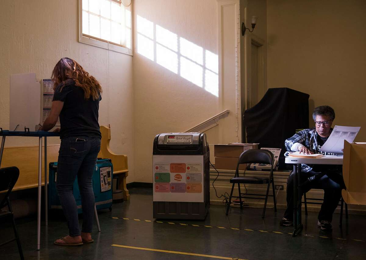 Meghan Driscoll, left, casts her vote in the Midterm Elections while poll worker Deborah Jackson organizes ballots at the Golden Gate Branch Library polling place in Oakland, Calif. Tuesday, Nov. 6, 2018.
