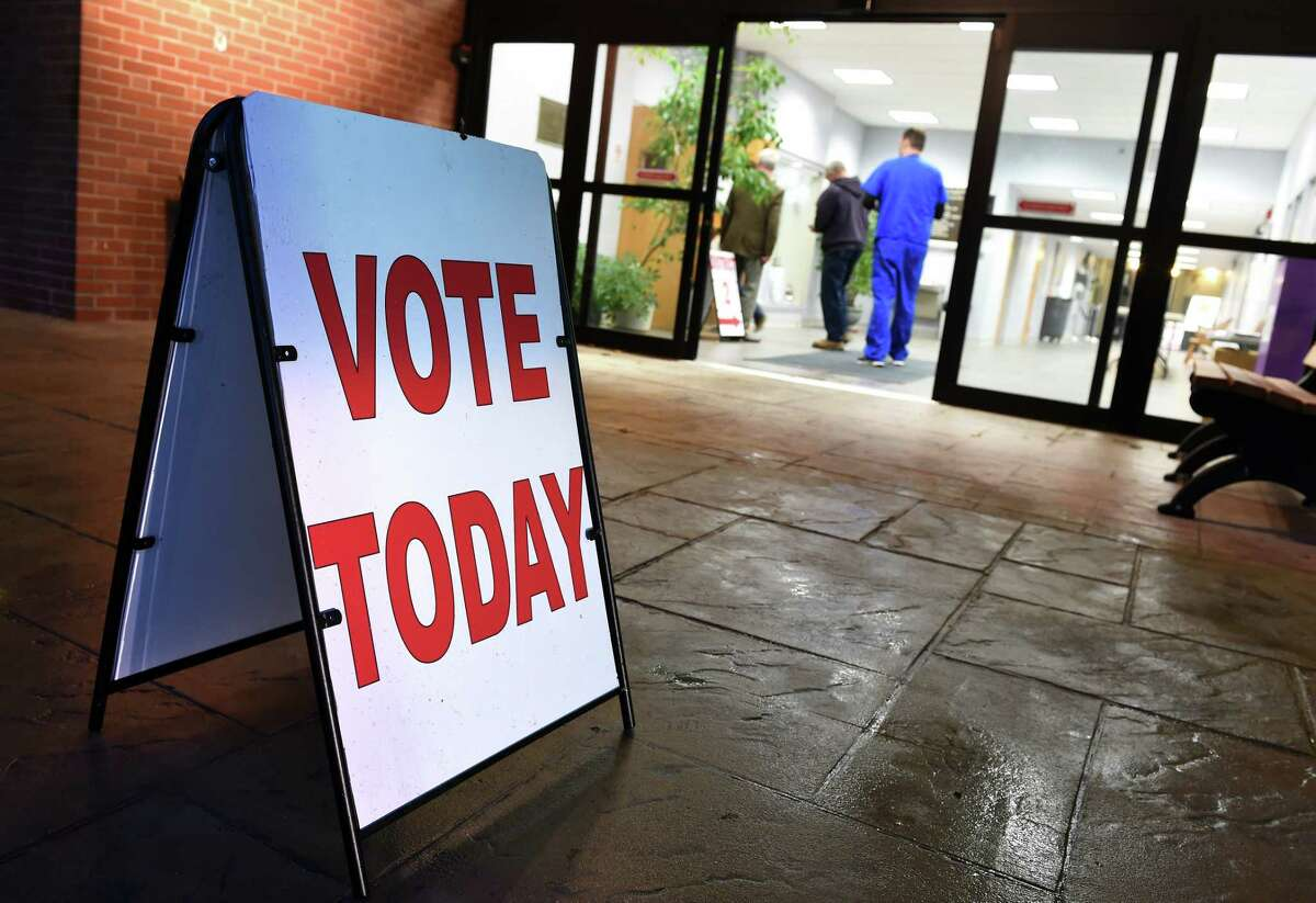 A sign encourages voting outside of polling places at the Orange Community Center on November 6, 2018.
