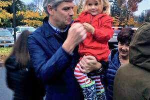 Bob Stefanowski held a niece Tuesday afternoon, at the Bristow Middle School in West Hartford, where he and his wife, Amy, seen at right, and three daughters joined his sister and her family at their neighborhood polling place.