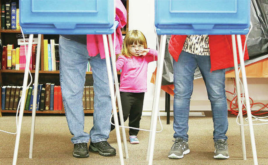 Two-year-old Alice Parks of Alton, who reminded her great grandmother and great grandfather to go vote Tuesday, gets a little bit fidgety as she stands between them in Alton Precinct Six at the Messiah Lutheran Church on Milton Road in Alton. Three Alton precincts vote at the church and were experiencing far more turnout Tuesday than a normal mid-term election, some racking up more votes by noon than they normally have in an entire election day. Photo: John Badman | The Telegraph