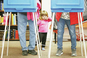 Two-year-old Alice Parks of Alton, who reminded her great grandmother and great grandfather to go vote Tuesday, gets a little bit fidgety as she stands between them in Alton Precinct Six at the Messiah Lutheran Church on Milton Road in Alton. Three Alton precincts vote at the church and were experiencing far more turnout Tuesday than a normal mid-term election, some racking up more votes by noon than they normally have in an entire election day.