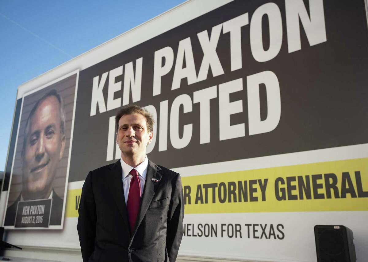 Texas Attorney General candidate Justin Nelson sets up his rolling billboard in downtown Tyler, Texas on Monday Oct. 29, 2018 for a press conference. Nelson is running against current Texas Attorney General Ken Paxton. The mobile billboard features Paxton's mug shot from three years ago when he was indicted and booked on felony fraud charges. (Sarah A. Miller/Tyler Morning Telegraph via AP)