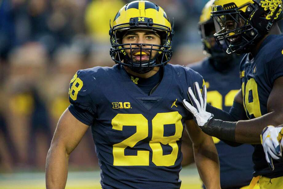 michigan defensive back brandon watson 28 celebrates with defensive lineman kwity paye right - Christmas Day College Football