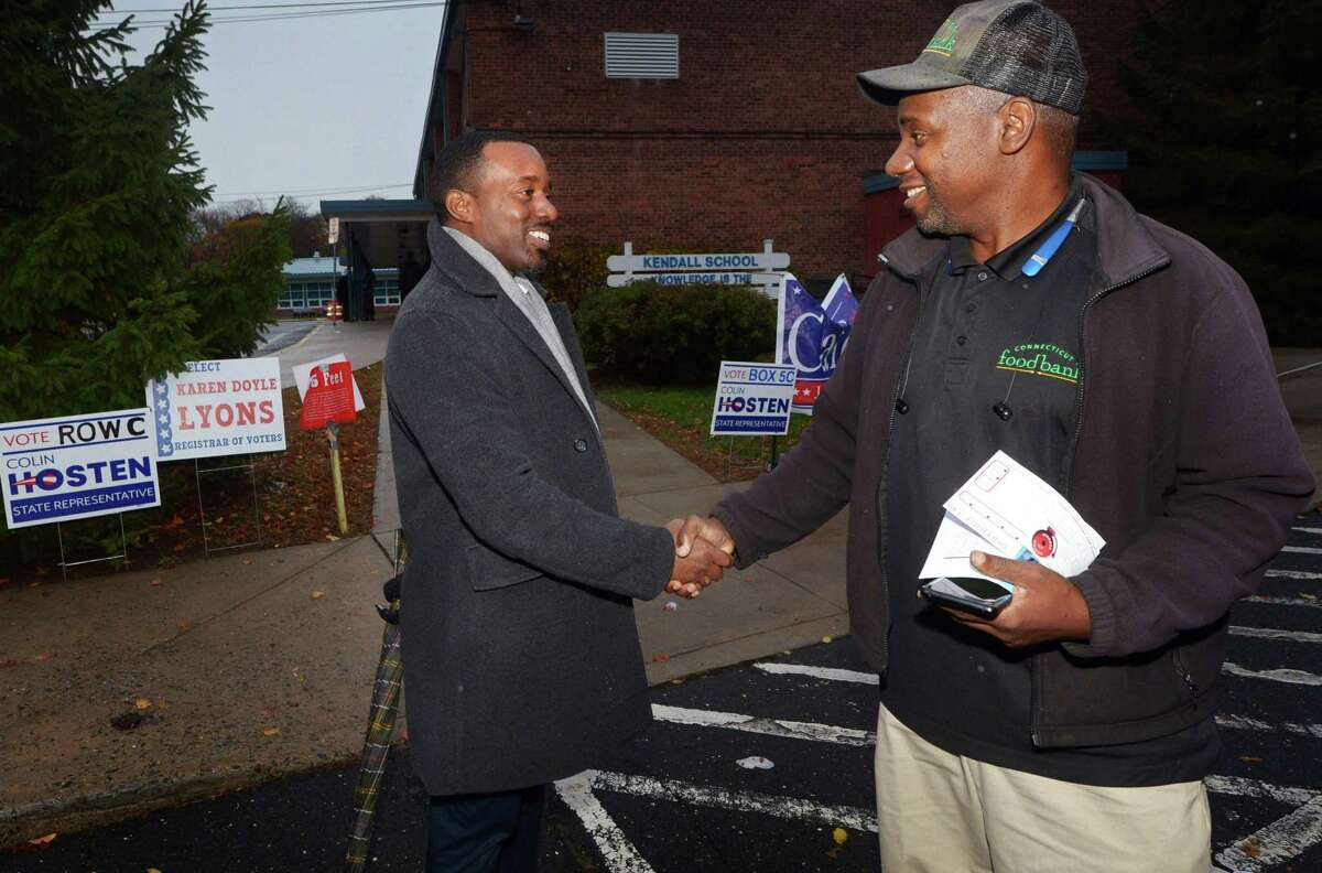 Working Familes candidate Colin Hosten greets Rodney Smith outside Kendall Elementary School as he campaigns for the 140th State Representative seat Tuesday, November 6, 2018, in Norwalk, Conn.