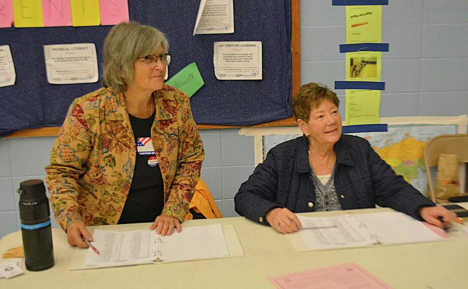 Poll workers at Macdonough Elementary School greet voters as they look up the addresses of residents in District 1 Tuesday morning. Photo: Cassandra Day / Hearst Connecticut Media