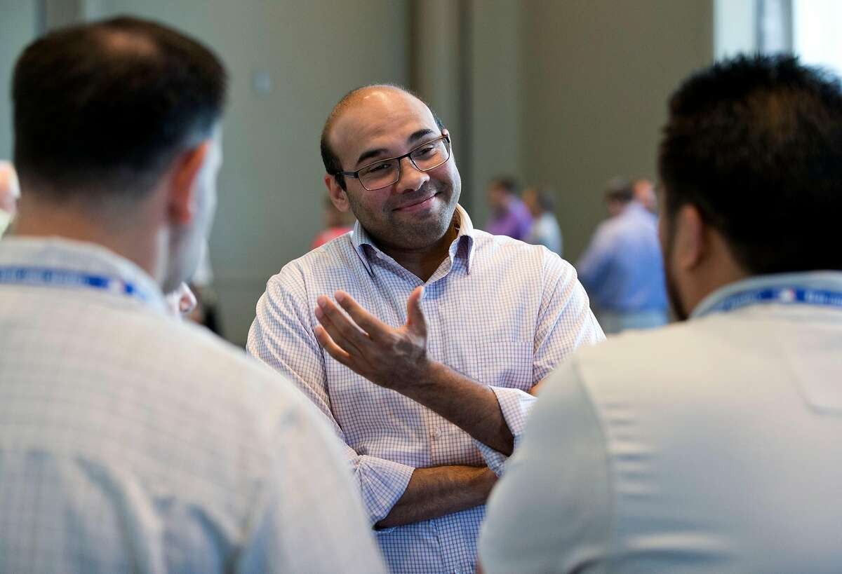 In this Wednesday, Nov. 11, 2015, photo, Los Angeles Dodgers general manager Farhan Zaidi, center, speaks to members of the media after attending the baseball general managers' meetings in Boca Raton, Fla. Major League Baseball's GMs have become the brainy bunch, the 30 current GMs include three Harvard graduates, two each from Cornell and Dartmouth, and one apiece from Princeton, Penn, MIT, Amherst, Georgetown and Wesleyan. Two have law degrees from Harvard, two earned MBAs at Northwestern and another has a Ph.D. from the University of California at Berkeley. Zaidi, hired by the Dodgers as GM in Nov. 2014, after a decade with Oakland, is an MIT graduate with a Ph.D. in economics from Cal. (AP Photo/Wilfredo Lee)