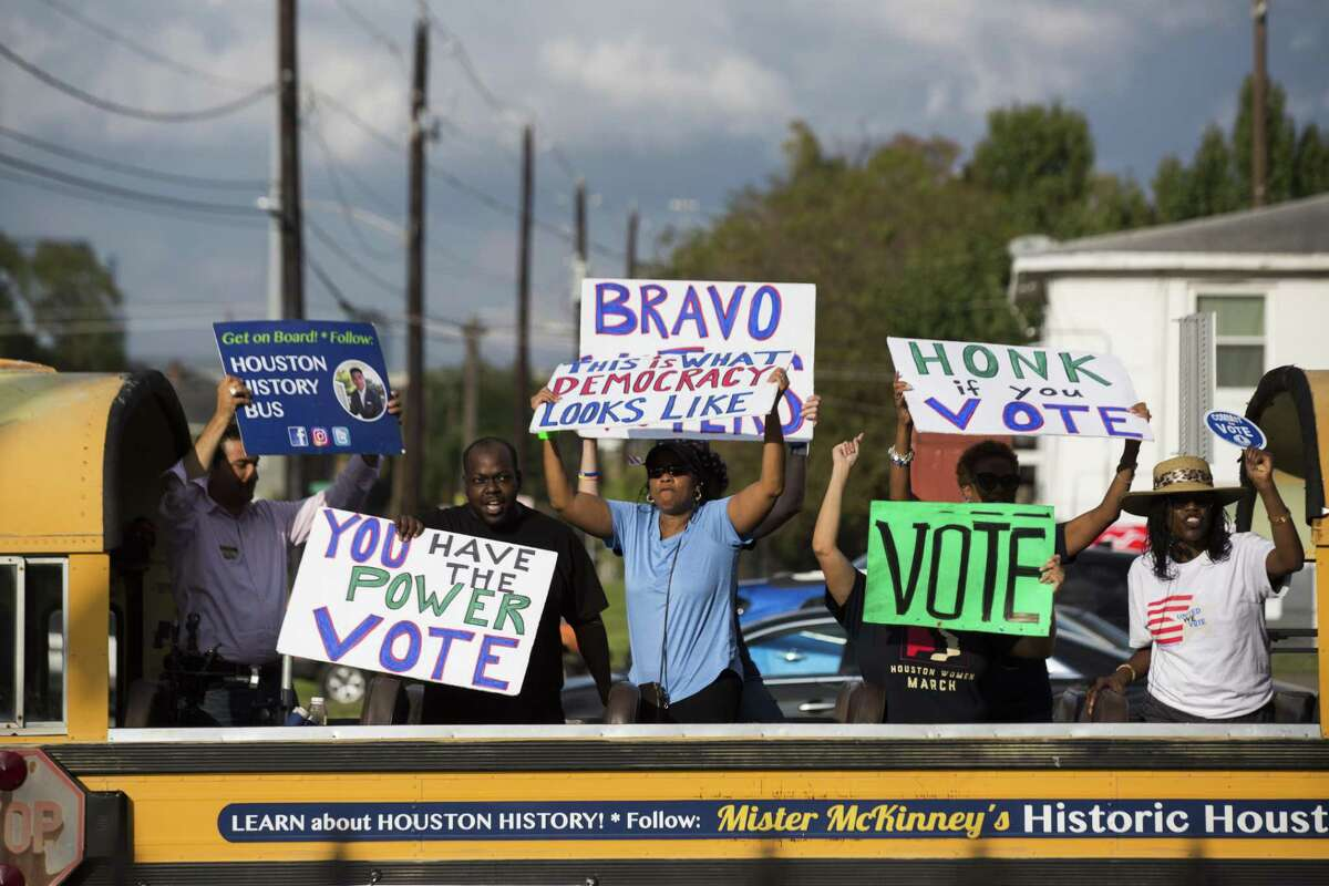 A bus with activists holding pro-voting signs drives by the NAACP Houston Branch where a press conference condemning an alleged altercation at a polling place takes place on Election Day, Tuesday, Nov. 6, 2018, in Houston.