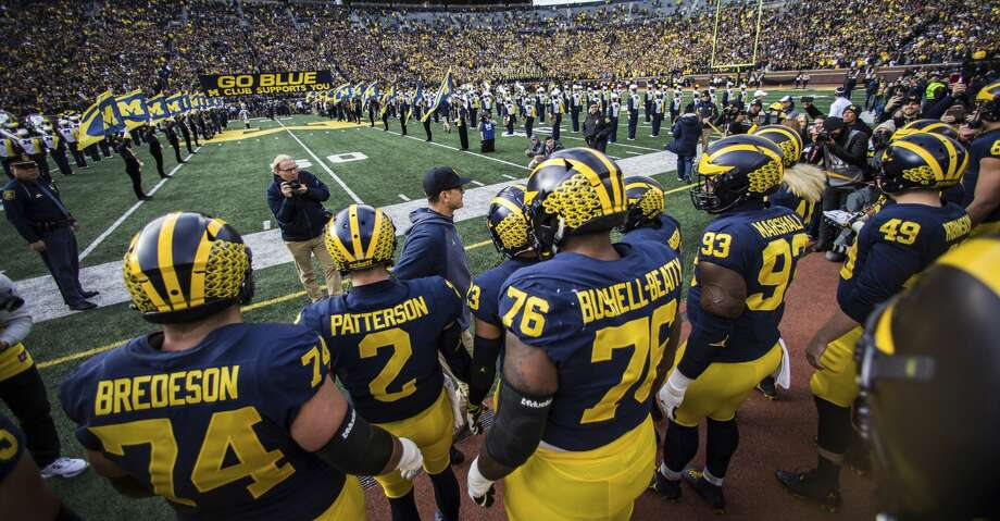 "Michigan head coach Jim Harbaugh, center, prepares to lead his players to run under the traditional ""GO BLUE"" banner before an NCAA college football game against Penn State in Ann Arbor, Mich., Saturday, Nov. 3, 2018. Michigan won 42-7. (AP Photo/Tony Ding) Photo: Tony Ding/Associated Press"