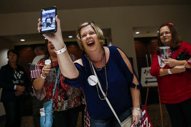 Shelia Tackett laughs as she sees a man she took a photo of at an event with President Donald Trump before the election night event for Senator Ted Cruz at the Hilton Post Oak Ballroom Tuesday, Nov. 6, 2018, in Houston.