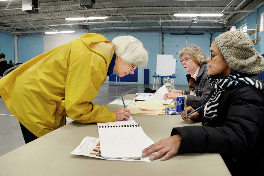 Susan DuBois, left, signs in to vote with election inspectors Wendy Lindskoog and Joanna Puertas, right, at the Parks & Recreation Department Tuesday Nov. 6, 2018 in Albany, NY.  (John Carl D'Annibale/Times Union) Photo: John Carl D'Annibale / 20045398A