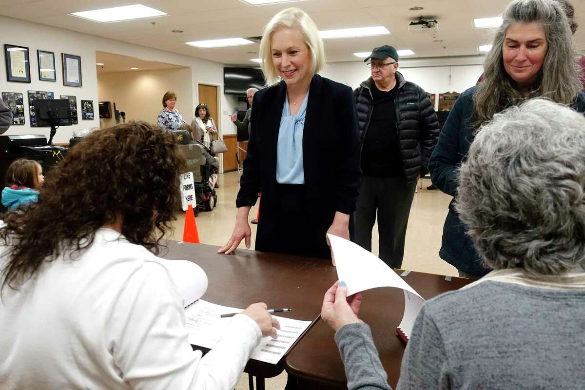 U.S. Sen. Kirsten Gillibrand, left, checks in to vote at the Brunswick Fire Co. No 1 on Tuesday, Nov. 6, 2018, in Troy, N.Y. She was facing a challenge from Republican Chele Farley. (Paul Buckowski/Times Union)