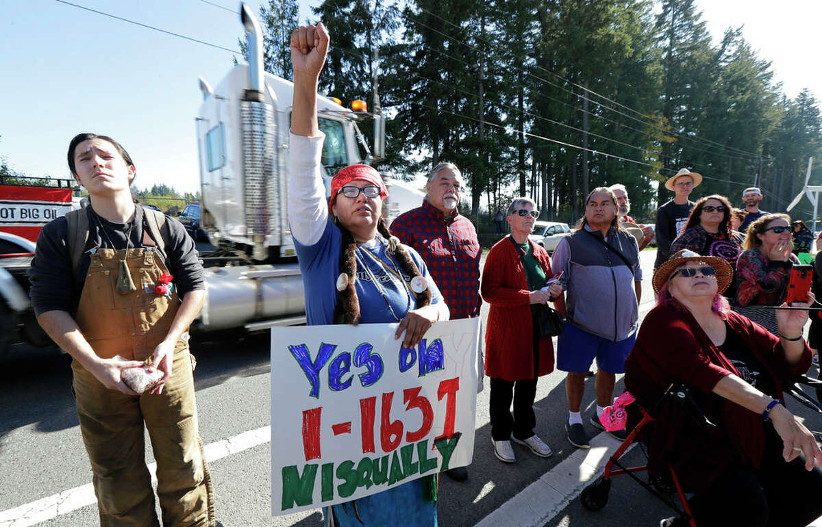 FILE - In this Oct. 17, 2018, file photo, a supporter of Initiative 1631 holds a sign referencing the Nisqually Indian Tribe during a rally supporting I-1631, a November ballot measure in Washington state that would charge a fee on carbon emissions from fossil fuels. Money has poured into the state for the campaign against I-1631, mostly from oil companies. (AP Photo/Ted S. Warren, File)