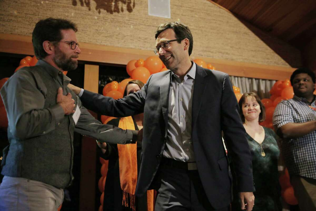 Washington State Attorney General Bob Ferguson, right, greets citizen bill sponsor and father to a gun violence survivor Paul Kramer as supporters of Washington State Initiative 1639, which will enact waiting periods and background checks on the purchase of semiautomatic weapons, increase the minimum age of semi-automatic weapon purchase from 18 to 21 and add class-C felony charges for any owner whose gun is used by an unlicensed party, gather at the Edgewater Hotel, Tuesday, Nov. 6, 2018. Early ballot drops show the Initiative has a solid lead. It will be the most comprehensive gun control legislation in any state.