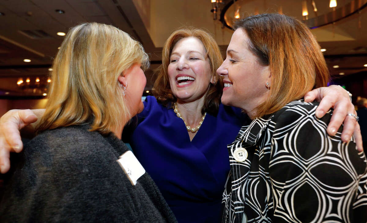 Democratic congressional candidate Kim Schrier, center, embraces supporters Jenell Tamaela, left, and Dana Rundle at an election night party for Democrats Tuesday, Nov. 6, 2018, in Bellevue, Wash. (AP Photo/Elaine Thompson)