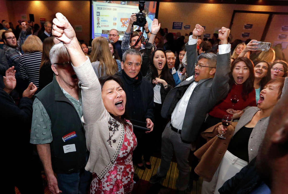 Washington State House candidate My-Linh Thai, left front, cheers with others as returns for another race come in at an election night party for Democrats Tuesday, Nov. 6, 2018, in Bellevue, Wash. (AP Photo/Elaine Thompson)