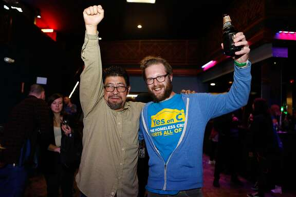 Evan Owski, a tech worker who rallied for Prop C, and Miguel Carrera, Organizer at the Coalition on Homelessness, celebrate at the Yes on C campaign watch party in the Mission District on Tuesday, November 6, 2018 in San Francisco, Calif.