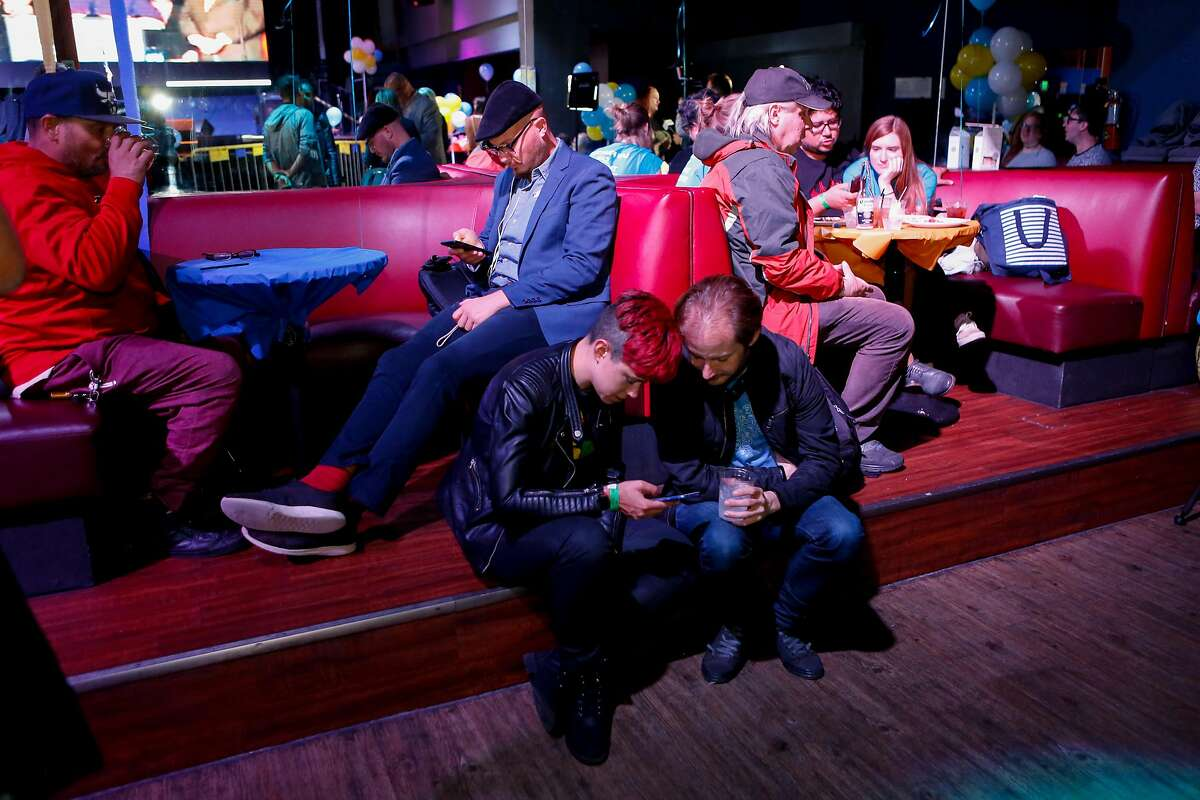 Supports check their phones for election results at the Yes on C campaign watch party in the Mission District on Tuesday, November 6, 2018 in San Francisco, Calif.