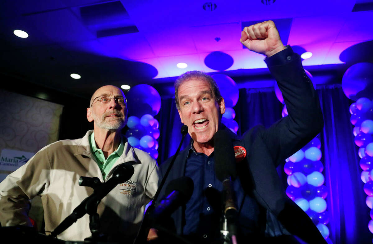 """Washington State representatives Larry Springer, left, and Roger Goodman speak to the crowd at an election night party for Democrats Tuesday, Nov. 6, 2018, in Bellevue, Wash. """"It is indisputable: Washington has the most regressive tax system in the nation,"""" Springer told a Seattle City Club legislative preview. (AP Photo/Elaine Thompson)"""