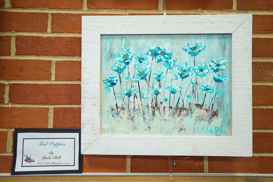 A painting by Linda Bell hangs in the mezzanine of the Grace A. Dow Memorial Library for an annual exhibit by the Paint and Palette group, featuring the work of local artists. (Katy Kildee/kkildee@mdn.net)