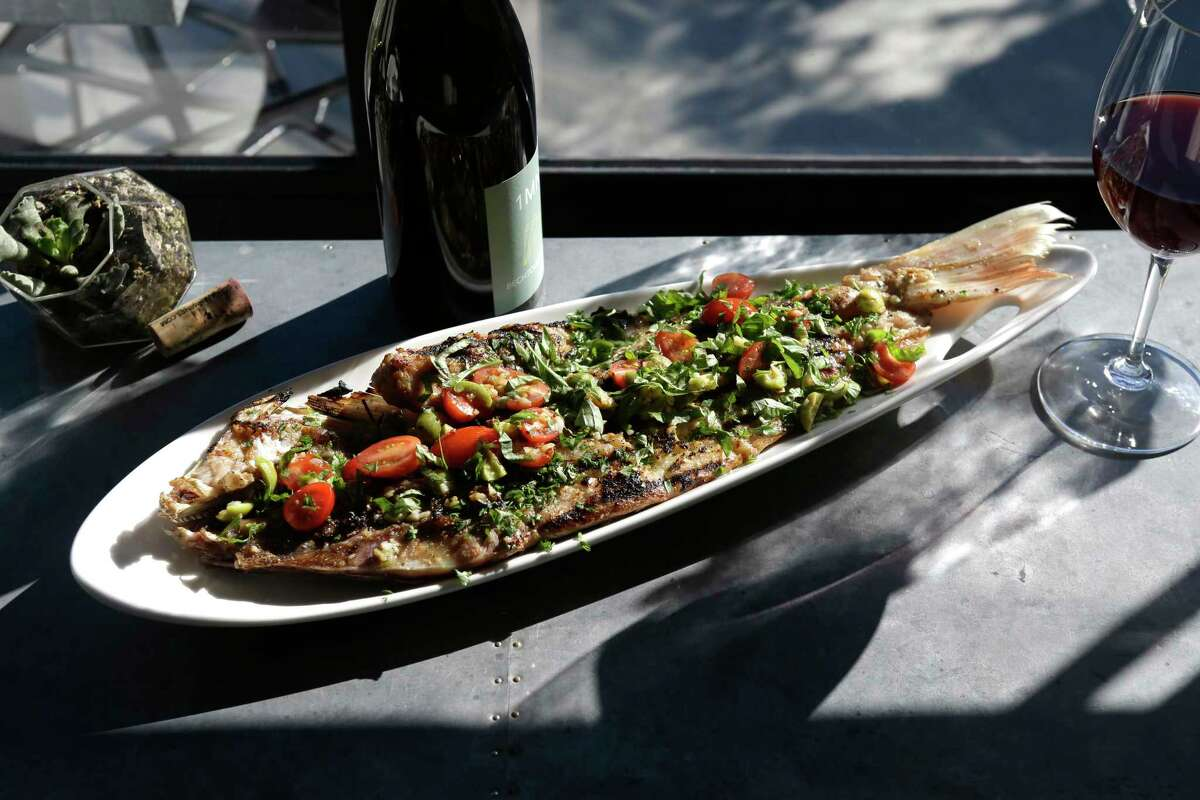 Half snapper topped with chopped mint, parsley, basil, olives and garlic at Avondale Food & Wine in Montrose.