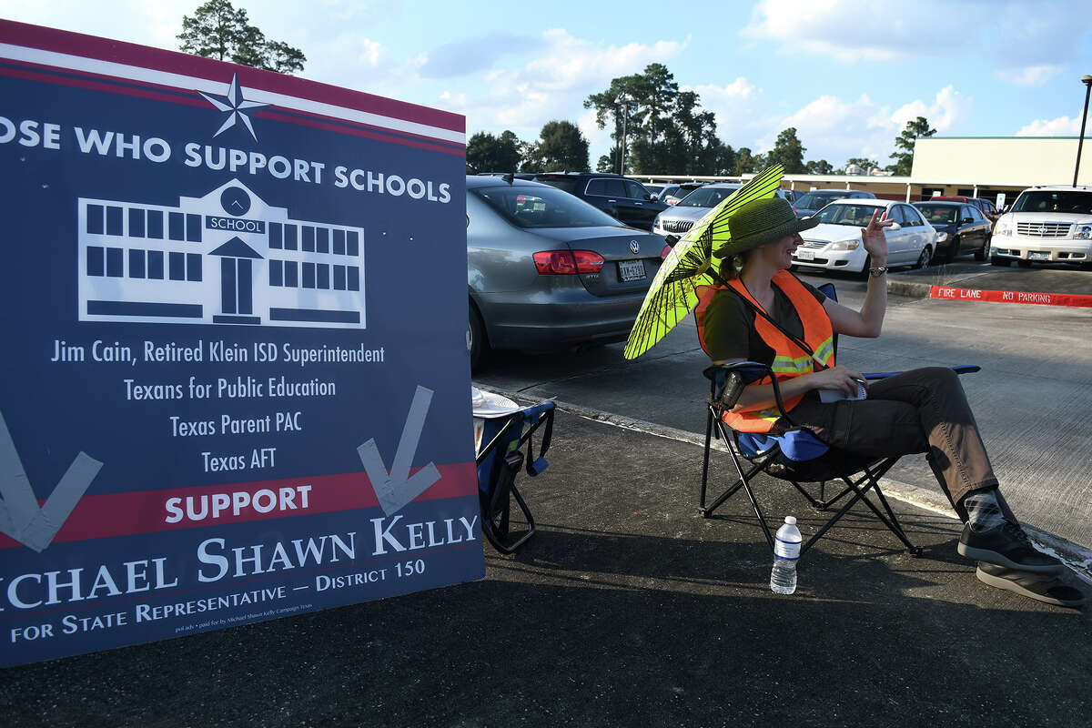 Elizabeth Jensen, of Spring and the Prcinct 912 Republican Part Chair, shows her support for State Representative District 150 Democratic candidate Michael Shawn Kelly with some last minute poll campaigning at McNabb Elem. School in Spring on Nov. 6, 2018.