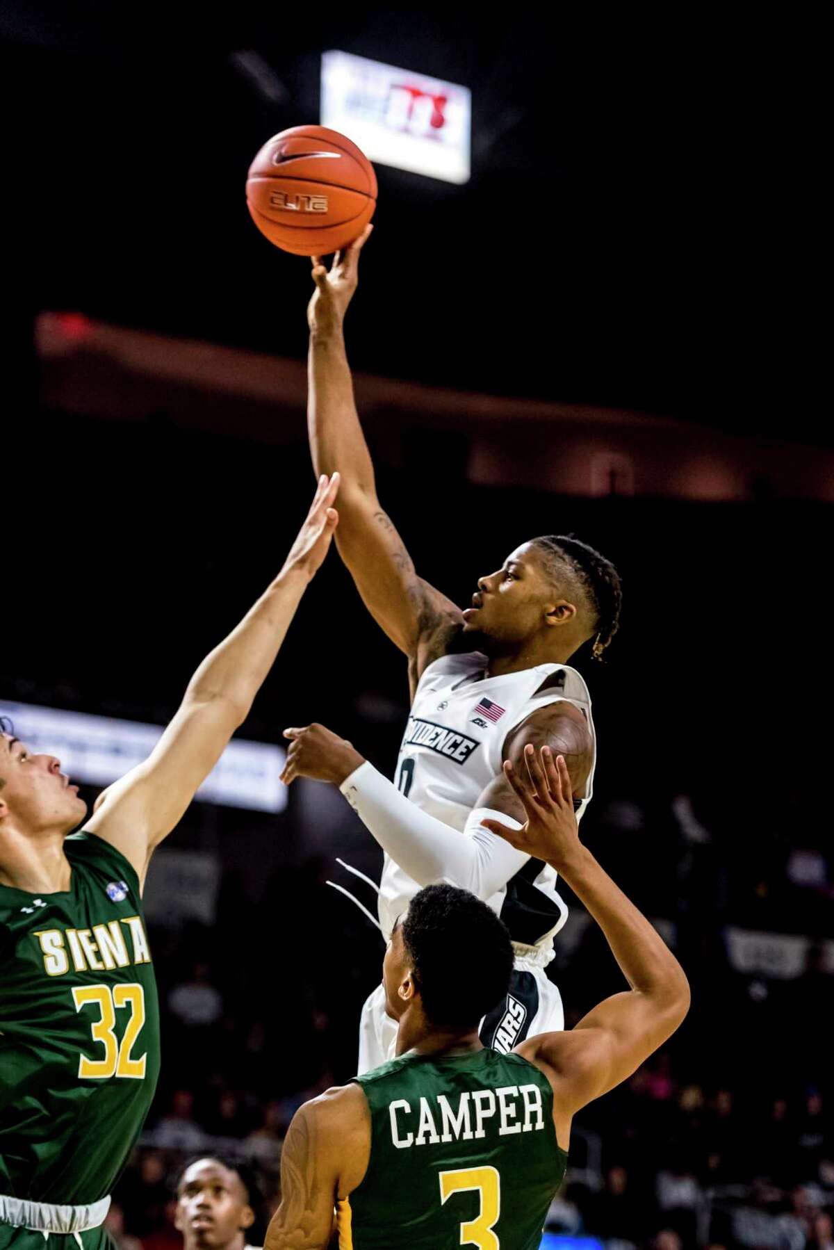 Nate Watson of Providence shoots over Siena?s Evan Fisher (32) and Manny Camper in Siena College men's basketball season opener Nov. 6, 2018, in Rhode Island.