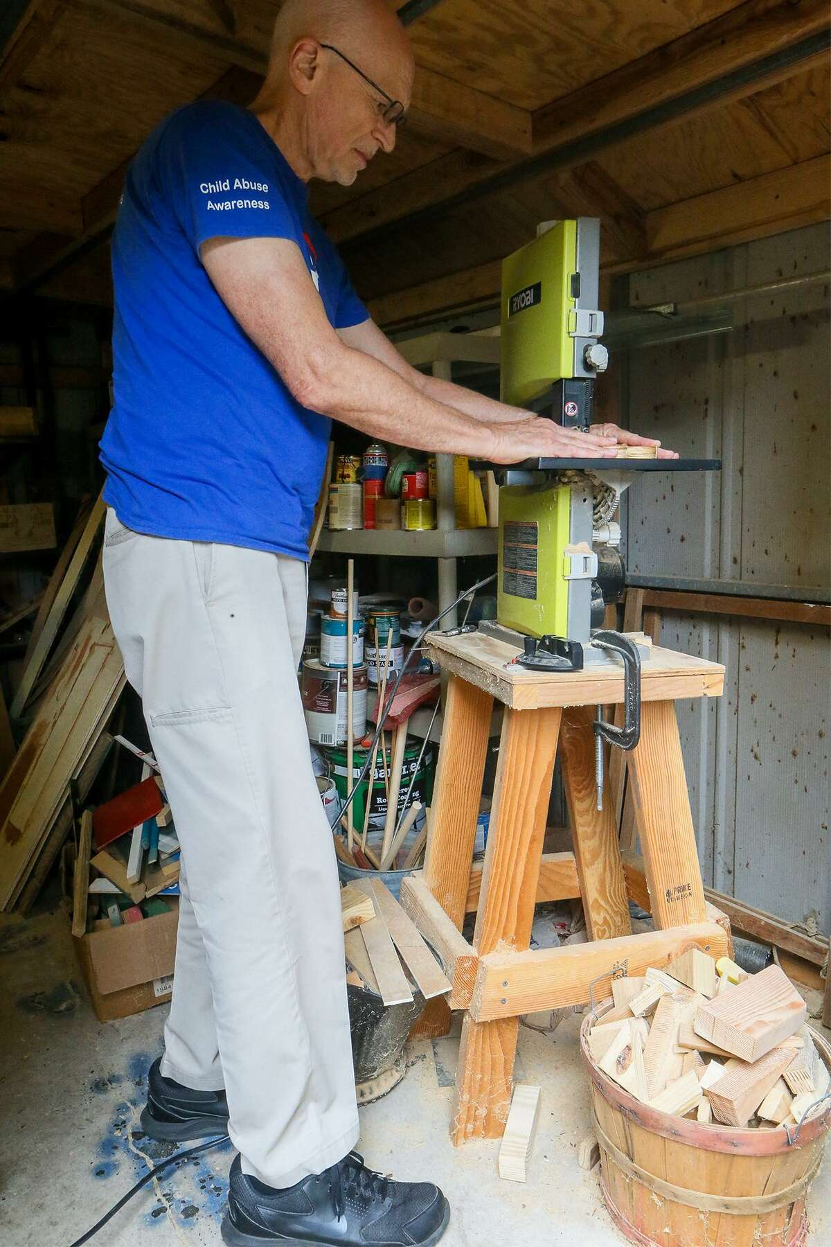 John Faultersack prepares to work with a band saw in his backyard workshop Nov. 5, 2018. Faultersack creates wooden toys and donates them to children in foster care.
