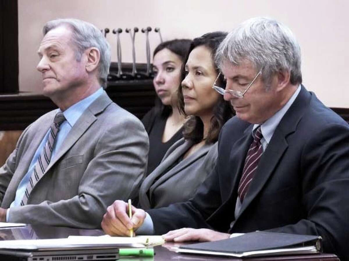 Bernadette Perusquia, second from right, sits with her defense attorneys as they listen to opening statements in her trial in the 49th District Courtroom on Tuesday.