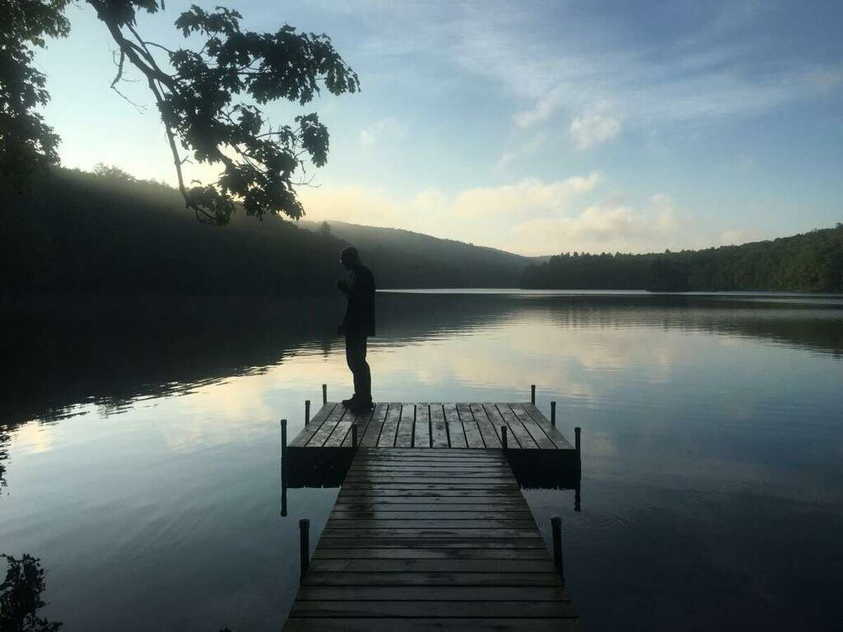 Carl Sevier has coffee on a pier on Upper Goose Pond in Massachusetts on the Appalachian Trail.