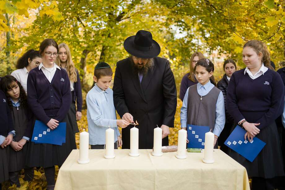 Rabbi Yehuda Teichtal lights candles with students to commemorate victims of the 1938 attacks. Photo: Markus Schreiber / Associated Press