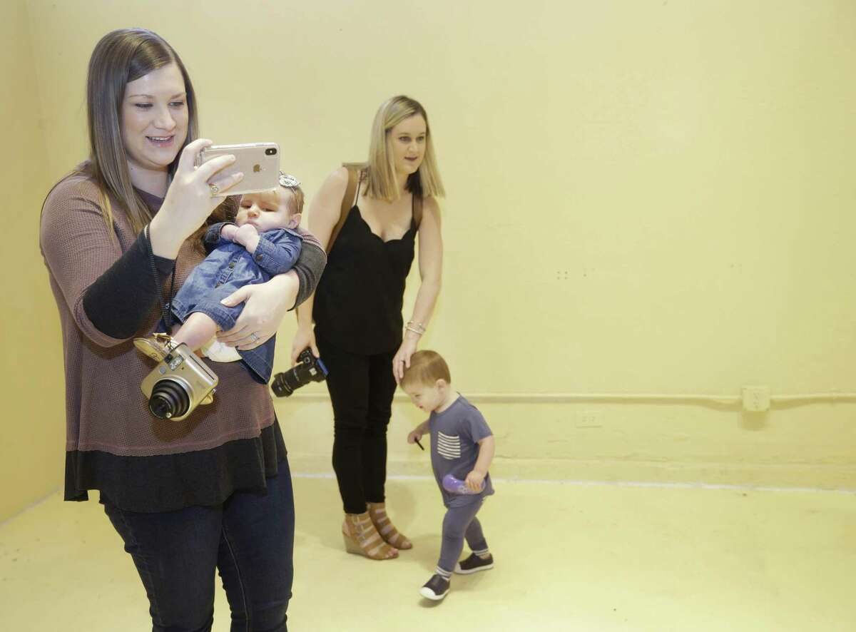Meredith Arthur, left, holds her 12-week-old daughter, Julie Arthur, as she and her friend, Erin Clayton, right, with her son, Parker Clayton, 1, take photos at the Flower Vault, 1735 Westheimer, a new pop-up shop Friday, Oct. 26, 2018, in Houston. The pop-up shop has several flower-themed rooms for self-service photo shoots.