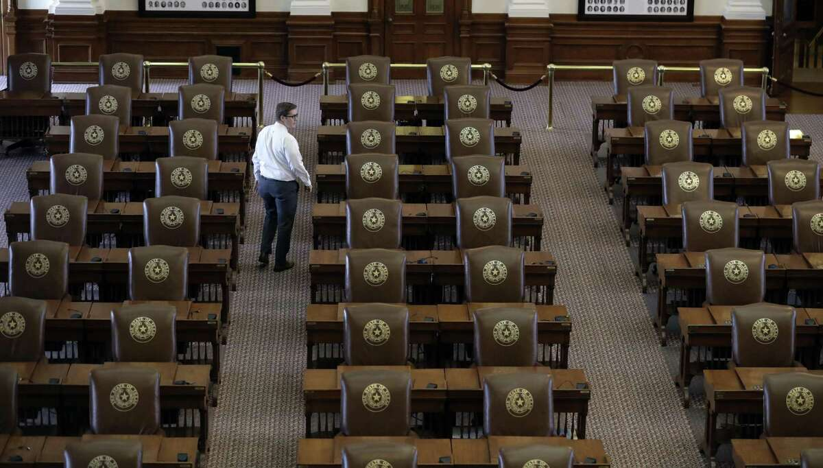 Chris Currens, who works in the office of the sergeant-at-arms in the Texas House, walks through an empty chamber, Wednesday, Aug. 16, 2017, in Austin, Texas. The Texas Legislature had adjourned Tuesday and a Texas